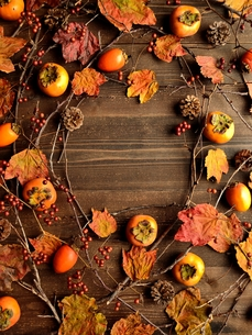 柿と枯葉のフレーム 木材背景の写真素材 [FYI01176723]