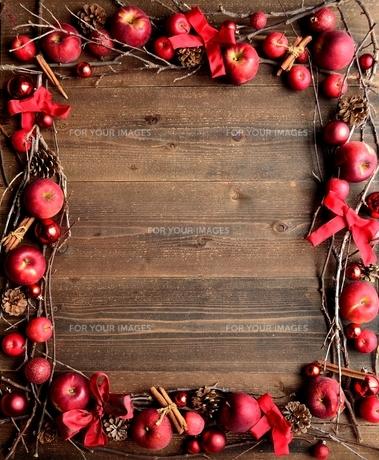 林檎とリボンとクリスマスオーナメント フレーム 黒木材背景の写真素材 [FYI01176730]