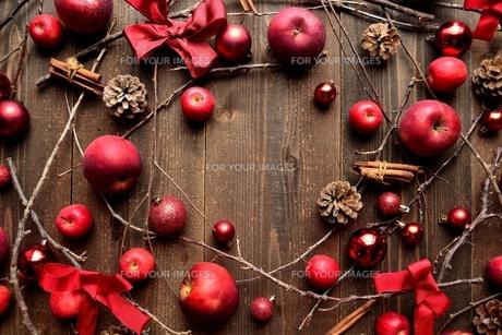 林檎とリボンとクリスマスオーナメント フレーム 黒木材背景の写真素材 [FYI01176746]