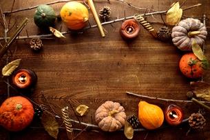 南瓜とキャンドルとまつぼっくり フレーム 木材背景の写真素材 [FYI01177004]
