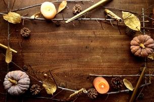 南瓜とキャンドルとまつぼっくり フレーム 木材背景の写真素材 [FYI01177020]