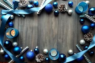 ブルーのクリスマスオーナメントとキャンドルのフレーム グレー木材背景の写真素材 [FYI01177059]