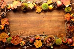 毬栗と柿と枯葉 フレーム 木材背景の写真素材 [FYI01177125]
