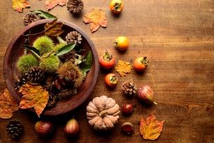 木製ボウルに盛った毬栗と柿とかぼちゃ 木材背景の写真素材 [FYI01177135]