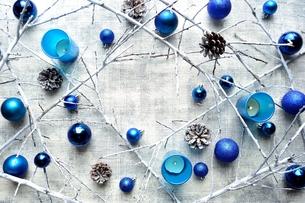ブルーのクリスマスオーナメントと枯枝とキャンドル フレームの写真素材 [FYI01177309]