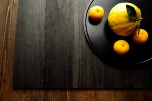 黒いおぼんにのせた鬼柚子と柚子の写真素材 [FYI01177348]
