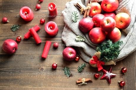 ニット生地に包んだ林檎とミニクリスマスツリーの写真素材 [FYI01177380]