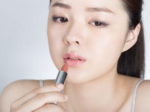 口紅を塗っている女性の写真素材 [FYI01177454]