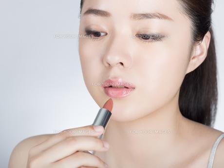 口紅を塗っている女性の写真素材 [FYI01177455]
