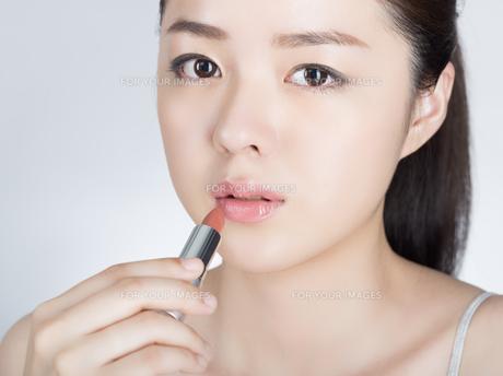 口紅を塗っている女性の写真素材 [FYI01177456]