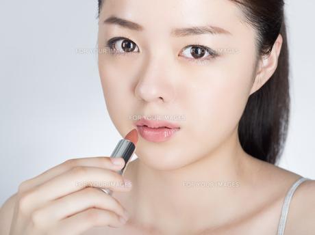 口紅を塗っている女性の写真素材 [FYI01177457]