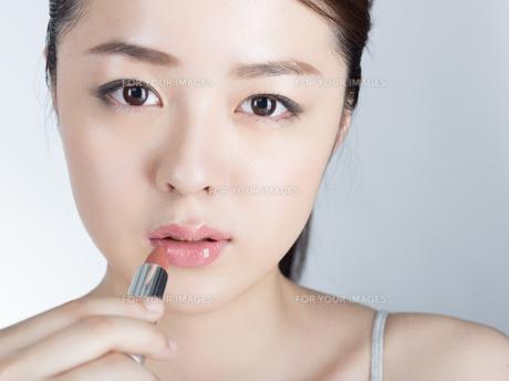 口紅を塗っている女性の写真素材 [FYI01177460]