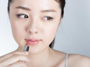 口紅を塗っている女性の写真素材 [FYI01177461]