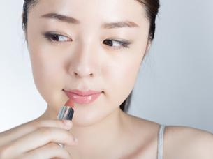 口紅を塗っている女性の写真素材 [FYI01177462]