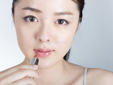 口紅を塗っている女性の写真素材 [FYI01177463]