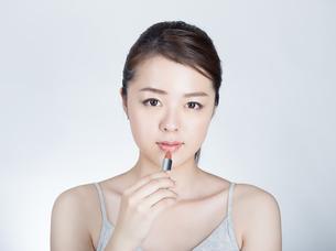 口紅を塗っている女性の写真素材 [FYI01177464]