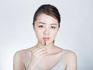 口紅を塗っている女性の写真素材 [FYI01177465]