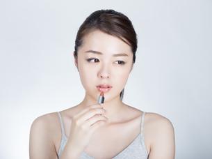 口紅を塗っている女性の写真素材 [FYI01177466]