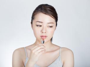 口紅を塗っている女性の写真素材 [FYI01177467]