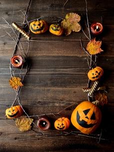 ハロウィンのかぼちゃと枯葉とキャンドルのフレーム 黒木材背景の写真素材 [FYI01177547]