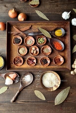 錆びたトレーに並べたスパイスとインド料理食材 黒木材背景の写真素材 [FYI01177576]