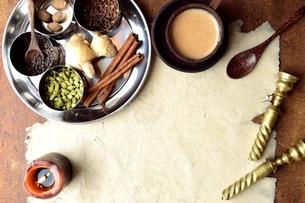 ステンレス食器に盛り合わせたスパイスと一杯のチャイと古紙の写真素材 [FYI01177583]
