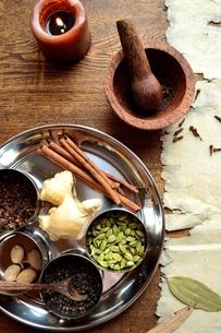 ステンレス食器に盛ったスパイスと木製すり鉢 の写真素材 [FYI01177587]