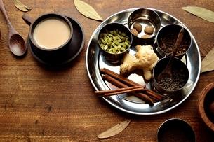 ステンレス食器に盛り合わせたスパイスと一杯のチャイ 木材背景の写真素材 [FYI01177590]