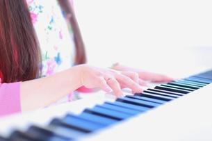 逆光でピアノを弾く女性の手もとの写真素材 [FYI01177867]