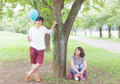 男女の若いカップルが笑顔で木を挟んでる 爽やかな二人の写真素材 [FYI01177877]