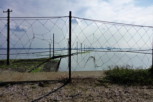 金網と海岸と電柱の写真素材 [FYI01179627]