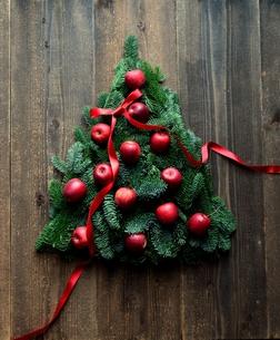 林檎とモミの木と赤いリボンのクリスマスツリー 黒木材背景の写真素材 [FYI01180049]