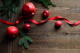林檎とザクロとモミの葉と赤いリボン 黒木材背景の写真素材 [FYI01180051]