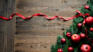 林檎とモミの木と赤いリボンのクリスマスツリー 黒木材背景の写真素材 [FYI01180053]