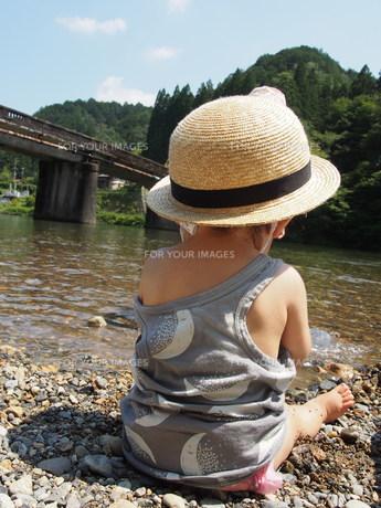 川辺で遊ぶ麦わら帽子を被った子供の後ろ姿の写真素材 [FYI01181441]