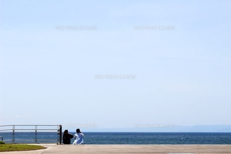 海の見えるデッキでのんびりと休日を楽しむカップルの写真素材 [FYI01181747]