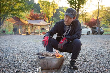 キャンプで肉を焼く男性の写真素材 [FYI01182798]