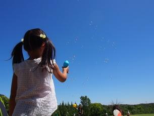 晴れた日に芝生の広場でしゃぼん玉をして遊ぶ子供の写真素材 [FYI01183454]
