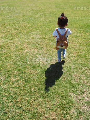 リュックを背負い芝生の上を歩くおだんご頭の子供の写真素材 [FYI01183460]