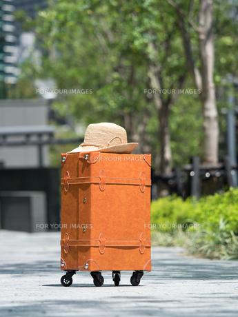 オフィス街に置いた旅行鞄の写真素材 [FYI01186992]