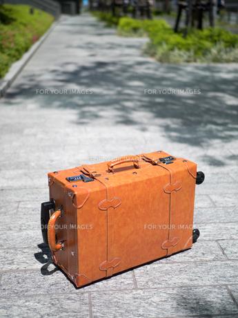 オフィス街に置いた旅行鞄の写真素材 [FYI01186993]
