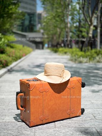 オフィス街に置いた旅行鞄の写真素材 [FYI01186994]