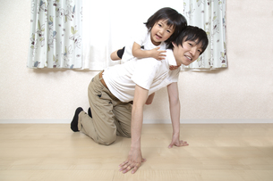 幼い娘と遊ぶ父親、幸せな家族シーンの写真素材 [FYI01187378]