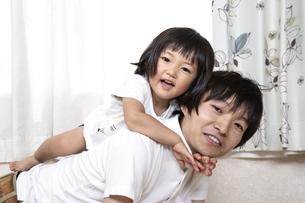 幼い娘と遊ぶ父親、幸せな家族シーンの写真素材 [FYI01187379]