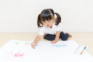 フローリングで絵を描く幼い女の子の写真素材 [FYI01187457]