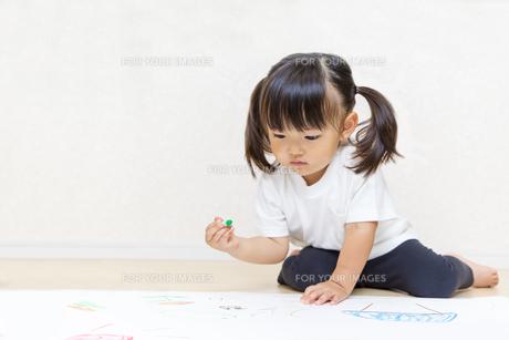 フローリングで絵を描く幼い女の子の写真素材 [FYI01187458]