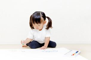 フローリングで絵を描く幼い女の子の写真素材 [FYI01187459]