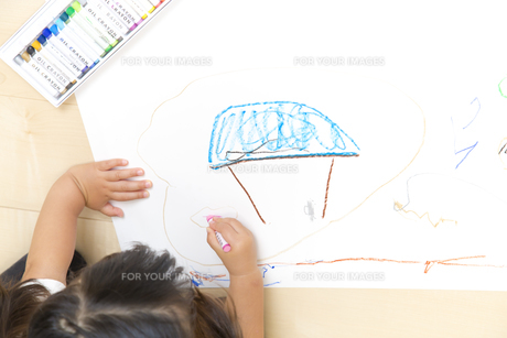 家の絵を描く幼い子の手元とコピースペースの写真素材 [FYI01187466]