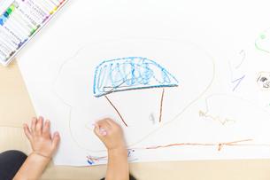 家の絵を描く幼い子の手元とコピースペースの写真素材 [FYI01187468]