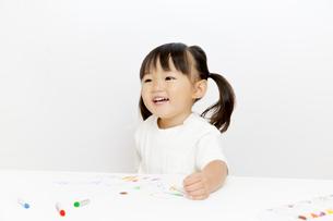 クレヨンで絵を描きながら微笑む幼い女の子の写真素材 [FYI01187477]